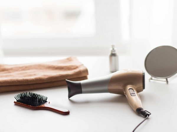 hair tools, beauty and hairdressing concept – hairdryer, brushes, mirror and towel on white background