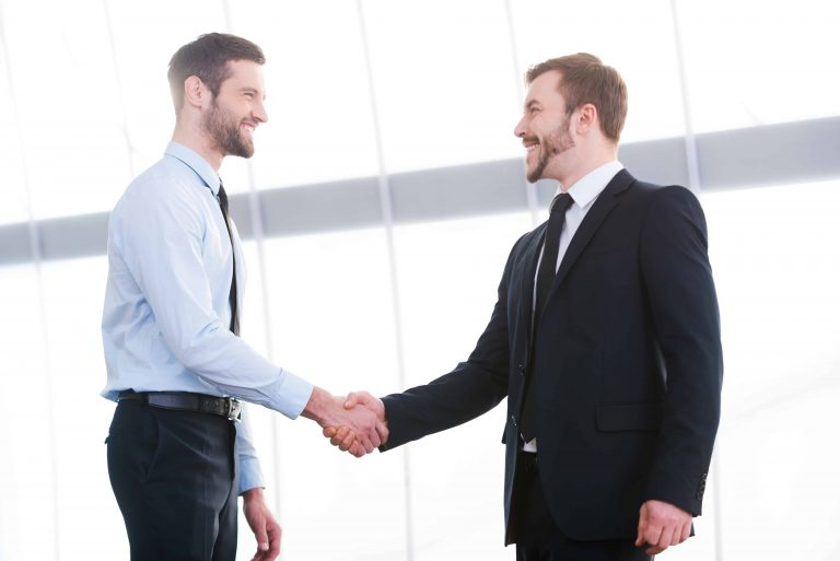 Two cheerful business men shaking hands and smiling while standing indoors
