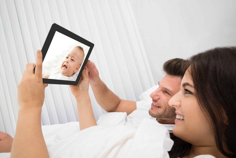 Young couple watching his baby on baby monitor