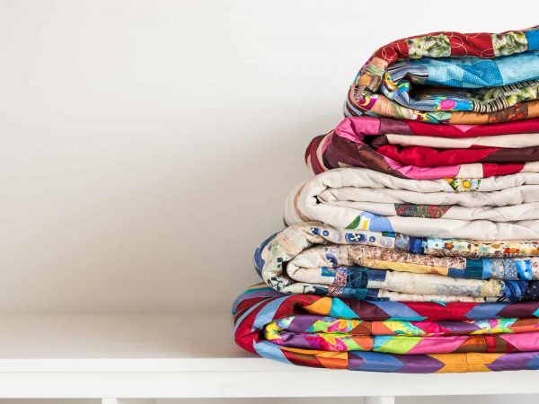 sewing and fashion concept – stack of colorful quilts, beautiful bedspreads stacked in several rows in height for storage, sale patchwork productions on a white background, copy space