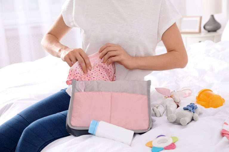 Woman packing baby accessories into maternity bag on bed,