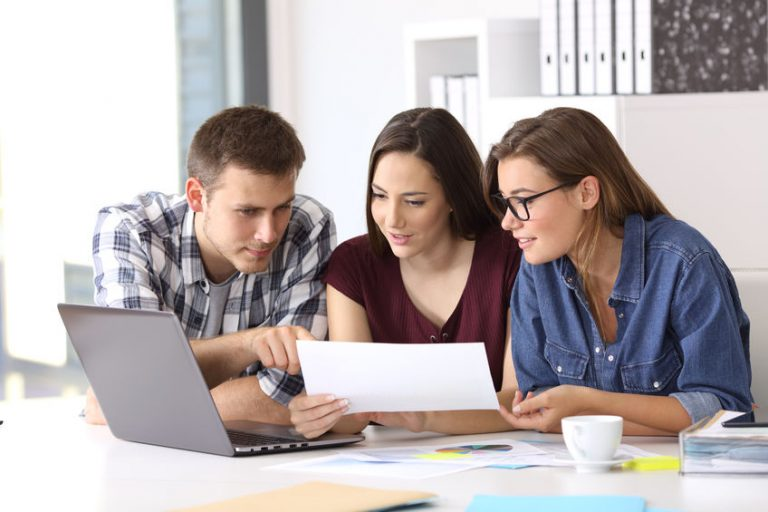 Three coworkers working at office comparing data