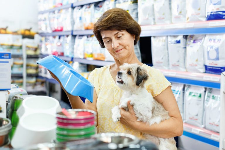 Mature woman choosing pet food bowl for her puppy in pet supplie