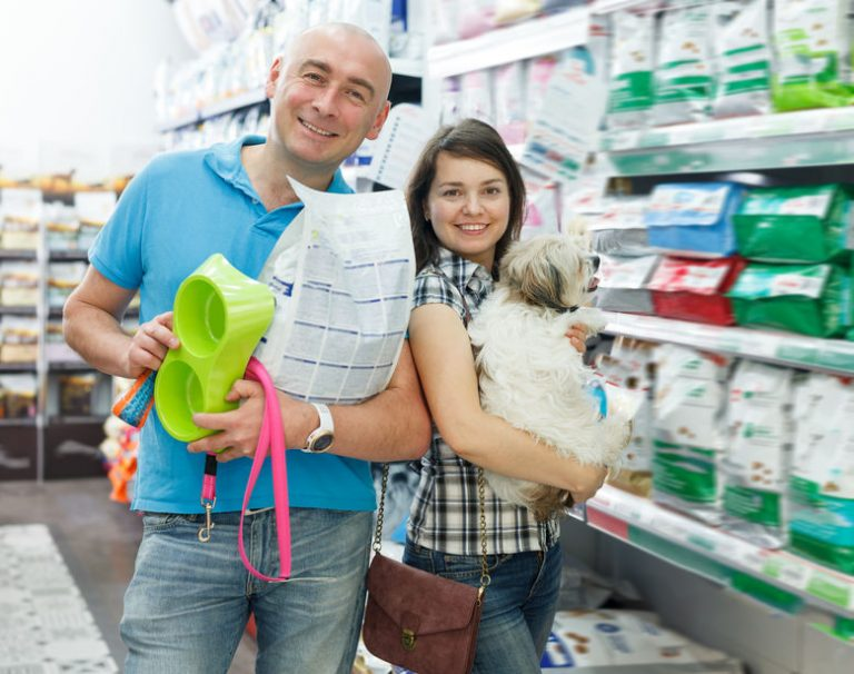 Portrait of adult couple with dog and purchases
