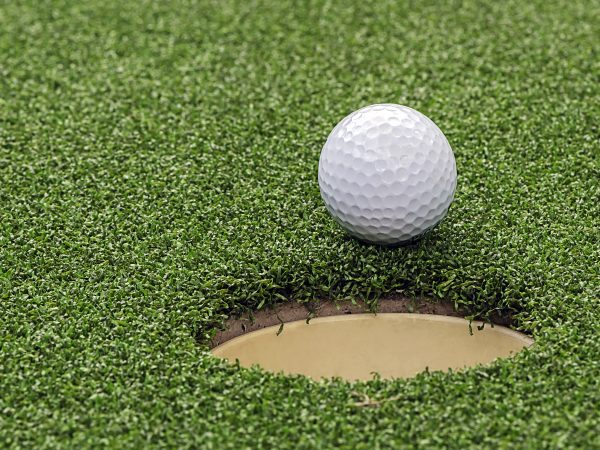 Golf ball on lip of cup,close up view.