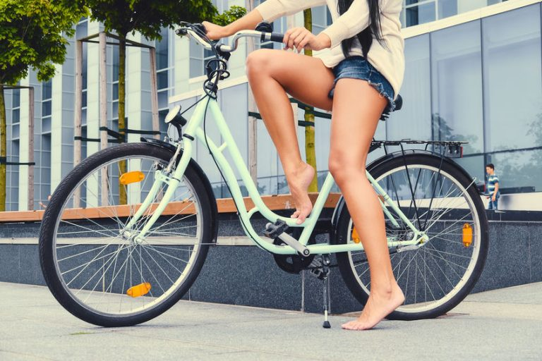 Woman's tan legs riding a bicycle over modern building backgroun
