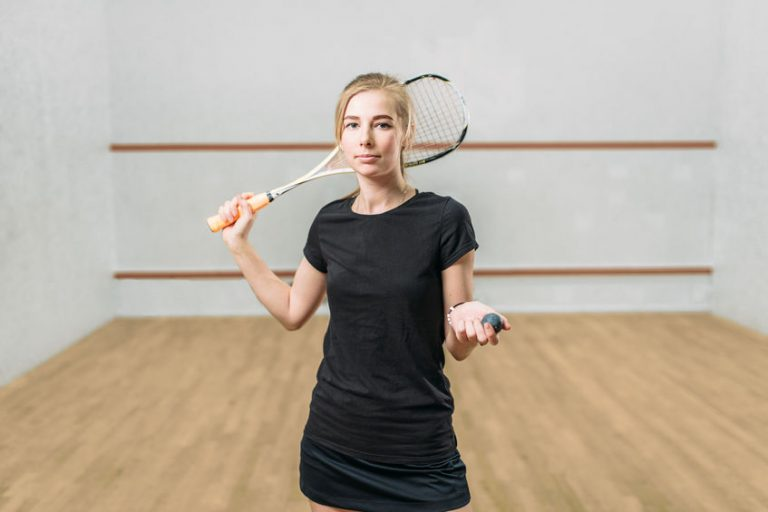Squash game female player with racket and ball