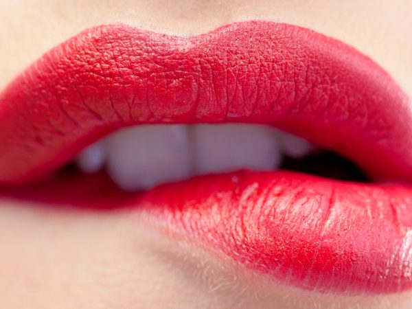 Close up on gorgeous model biting red lips on white background
