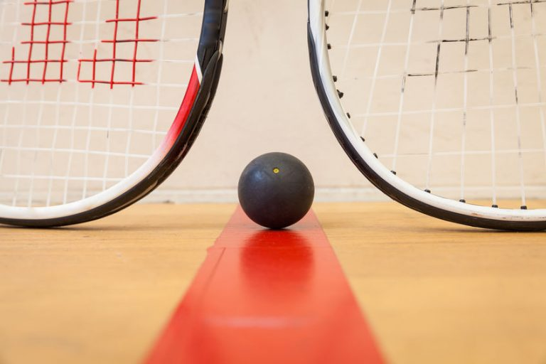 squash ball between two squash rackets
