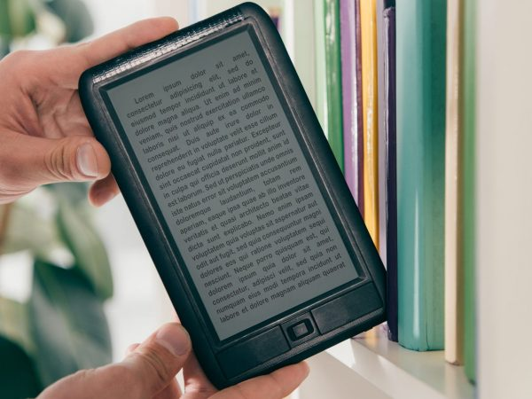 cropped view of man taking ebook from bookshelf
