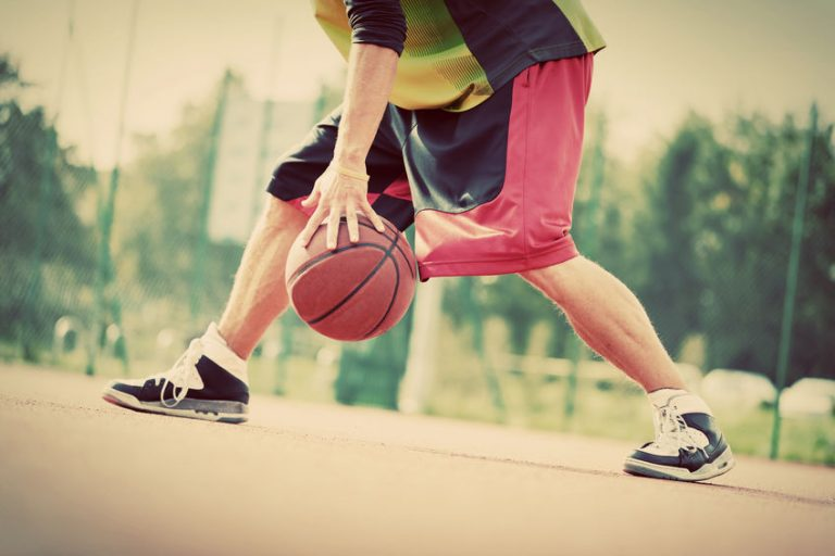 Young man on basketball court dribbling with ball. Vintage mood