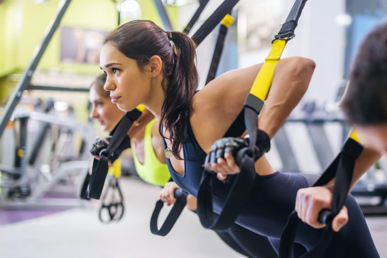 Women doing push ups training arms with trx fitness straps in the gym Concept workout healthy lifestyle sport.