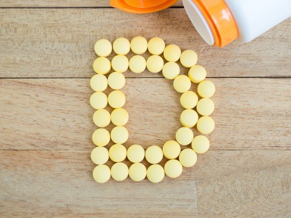 Yellow pills forming shape to D alphabet on wood background
