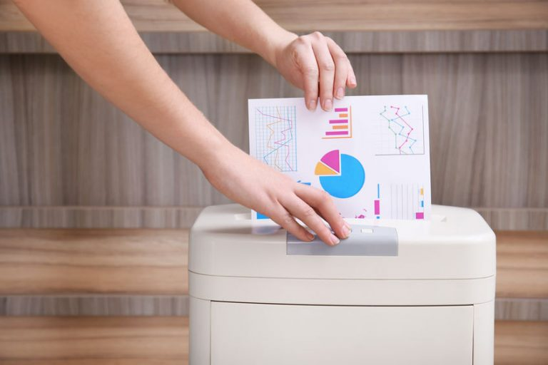 Woman destroying document with shredder in office