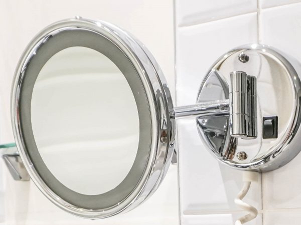 Round mirror at the wall Inside the bathroom