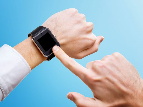 Businessman is pointing at smart hand with smart watch isolated at blue background.