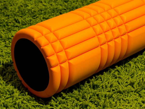 Orange foam roller on green carpet background
