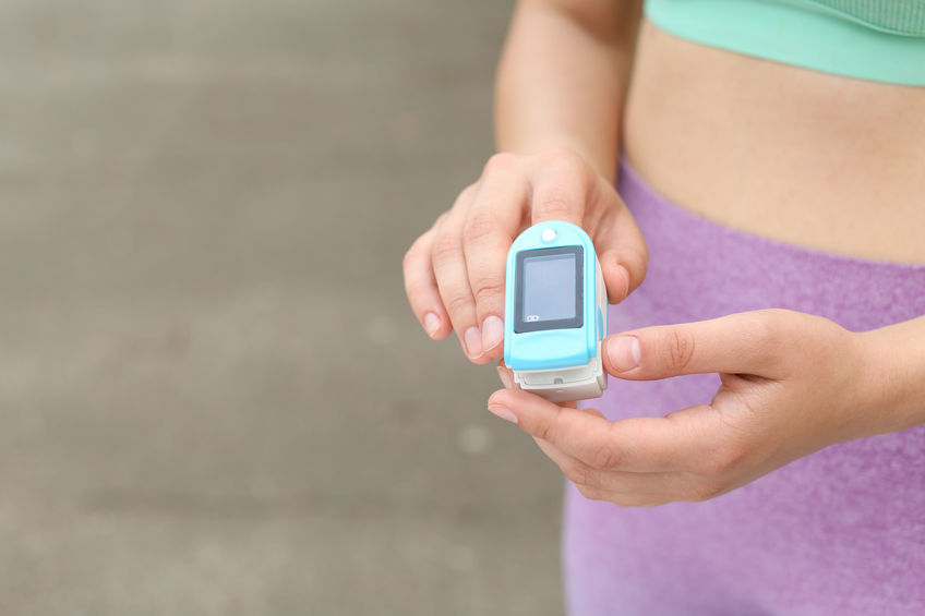 Young woman checking pulse with medical device after training on street, closeup. Space for text