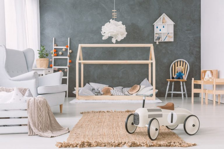 Lamp above wooden bed in grey baby's bedroom interior with car toy near armchair. Real photo