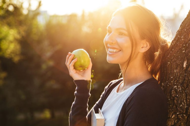 Beautiful young girl holding apple