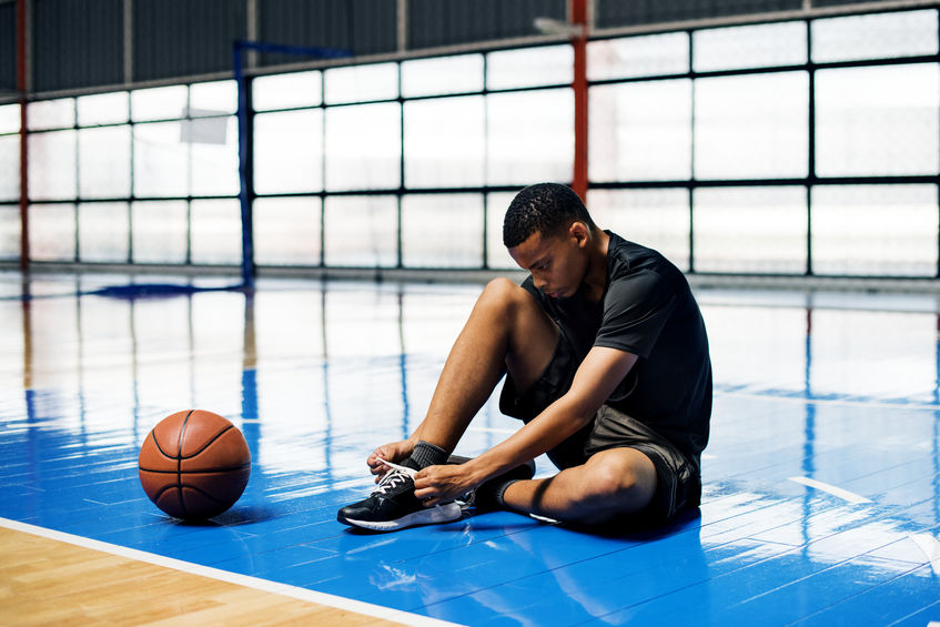 American teenage boy tying his shoelaces on a basketball court