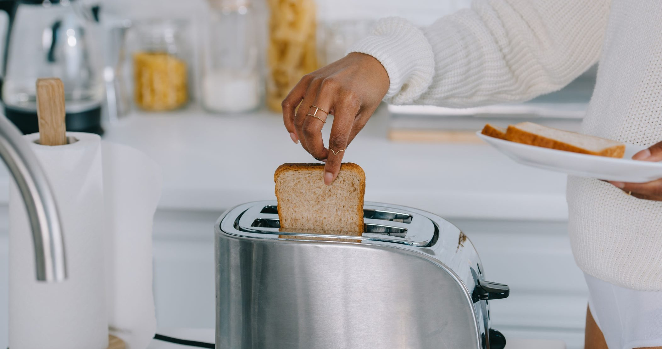 cropped shot of african american woman in underwear and sweater making toasts at kitchen