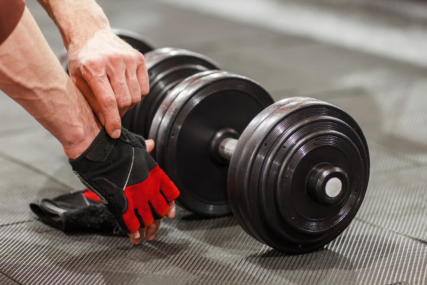 Image of a person lifting weights using gym gloves