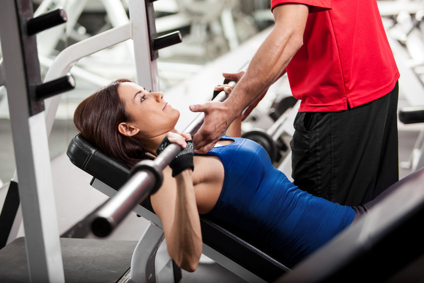 Image of a woman lifting weights helped by instructor in gym