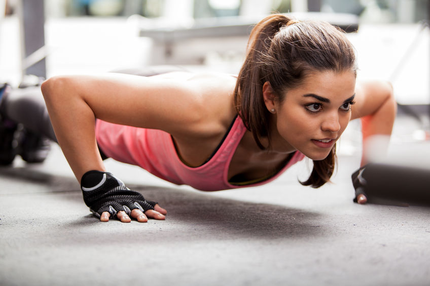 Woman doing push-ups using gym gloves