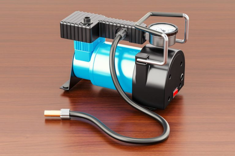 Car portable electric air compressor on the wooden table. 3D ren