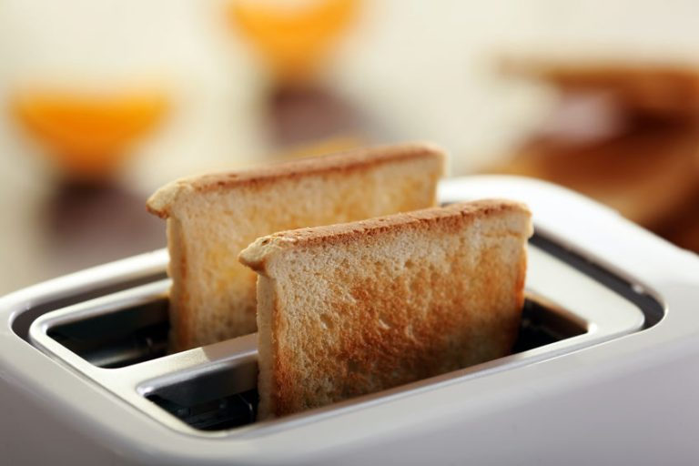 Served table for breakfast with toast and orange juice, on blurred background