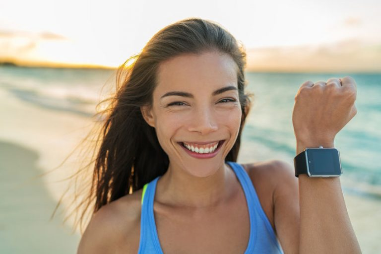 Woman on the beach with smartwatch