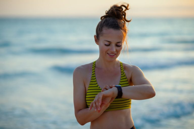 woman on beach exercising watching clock