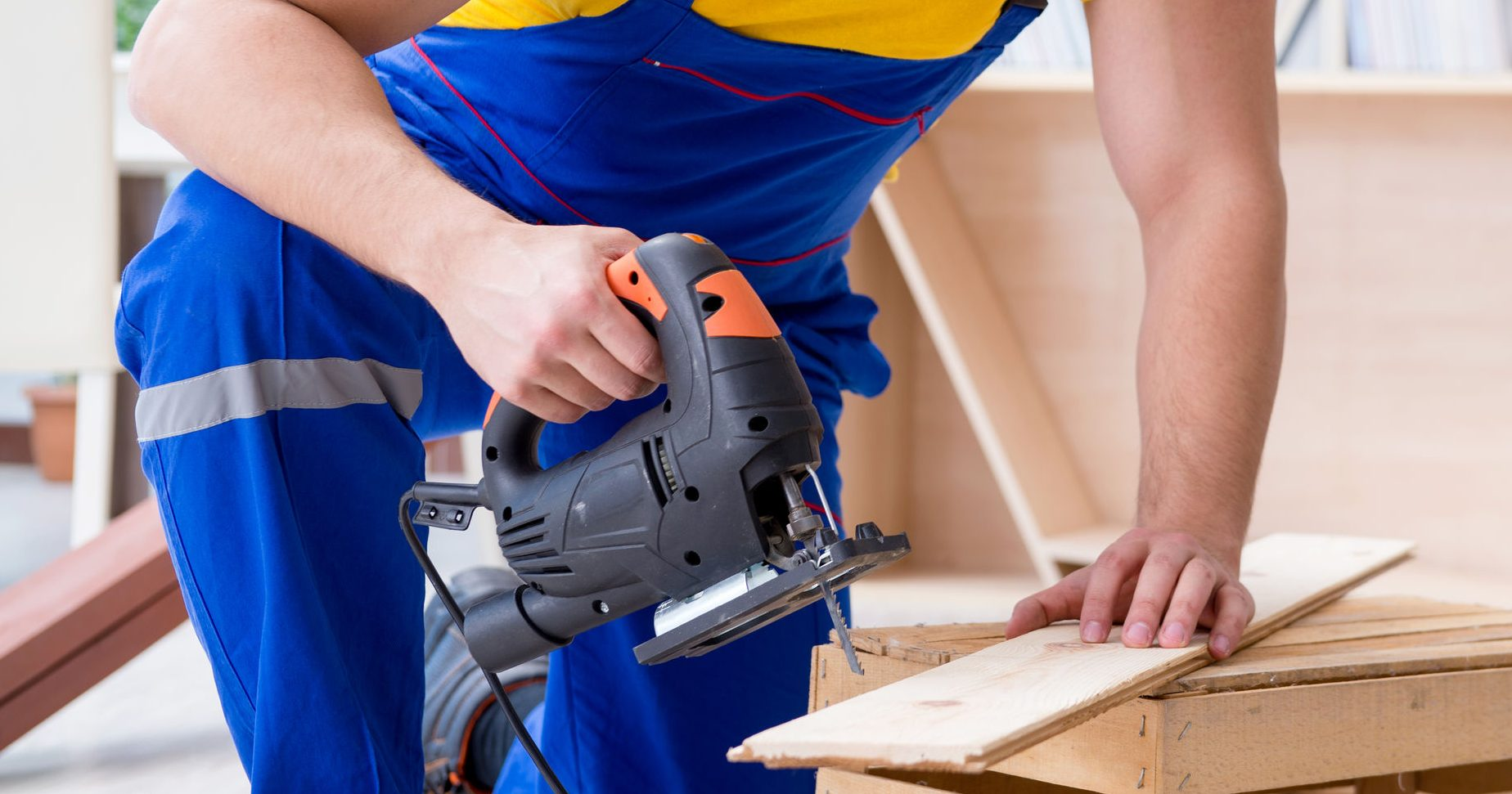Repairman carpenter cutting sawing a wooden board with an electric power saw