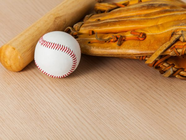 Baseball bat with ball and baseball glove on wood background