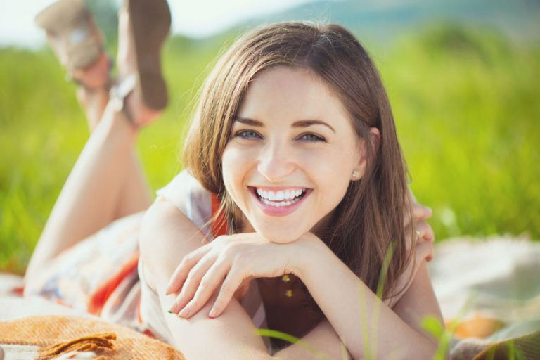 Portrait of a beautiful young smiling woman on grass