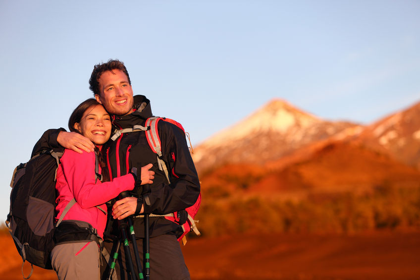 happy couple hiking enjoying looking at view embracing in love. hiker man and woman wearing backpacks enjoying sunset during hike