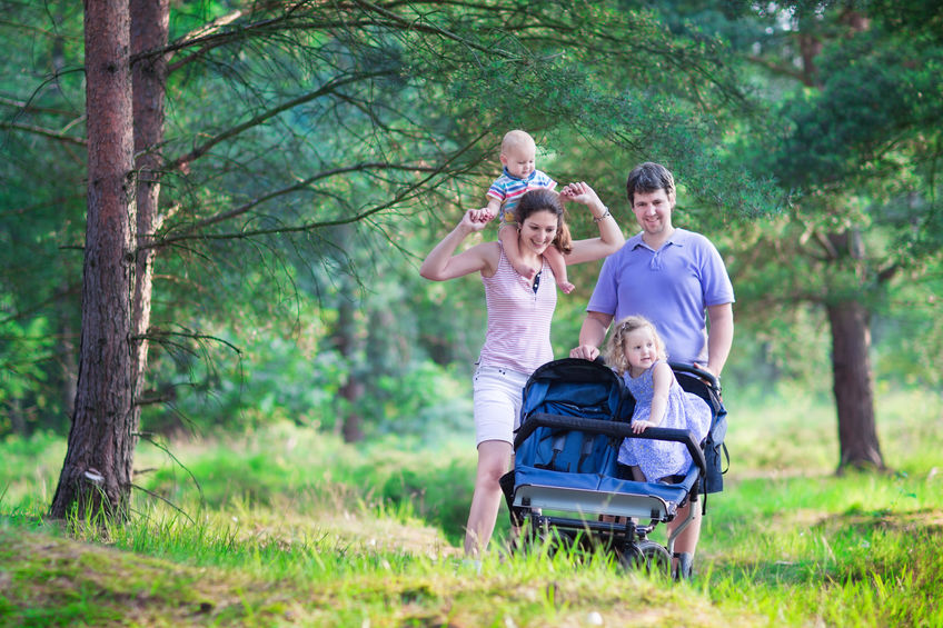 Active parent hiking with two kids in a stroller