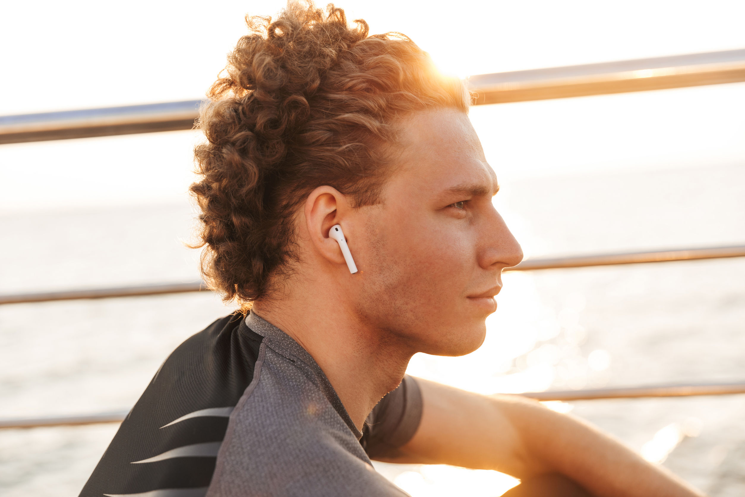 Close-up of a handsome young man playing music with wireless headphones outdoors