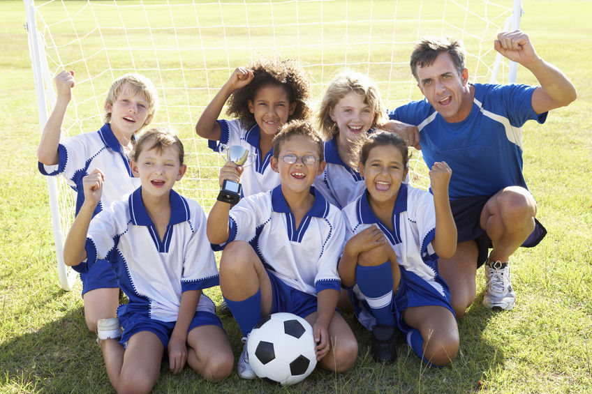 Group Of Children In Soccer Team Celebrating With Trophy