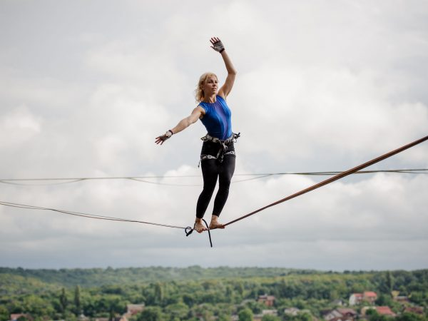 Young blondie woman balancing tilted her hands in the right direction on the slackline on the background of clear sky